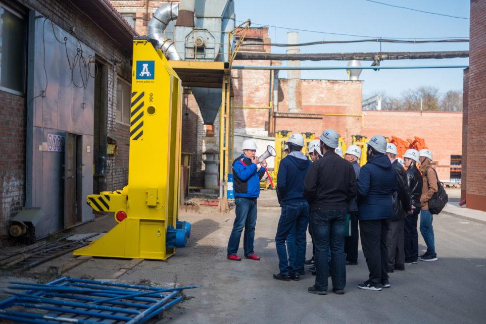 экскурсовод по заводу водит посетителей
